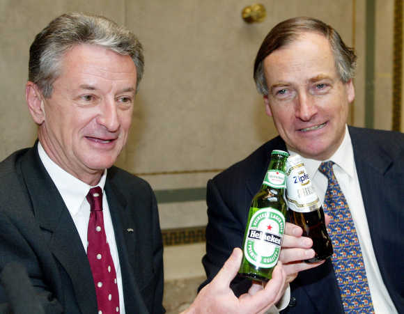 BBAG CEO Karl Buecher, left, and Heineken CEO Anthony Ruys toast with two bottles of beer in Vienna, in a file photo.