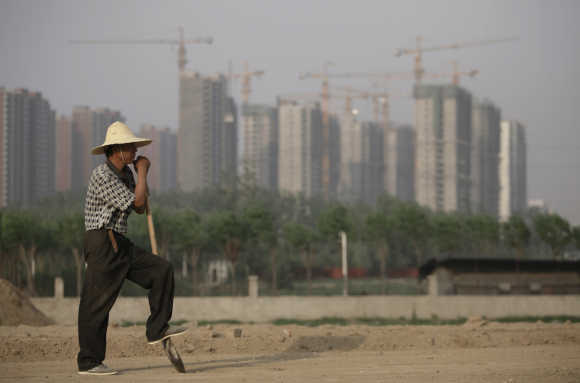 Worker rests on his shovel at a road construction site as cranes are seen in the background at a residential area under construction in Beijing.