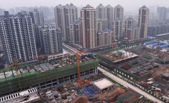 Newly constructed residential buildings are seen next to a construction site in Xi'an, Shaanxi province, China.