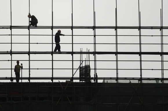 Labourers work on scaffolding at a residential construction site.