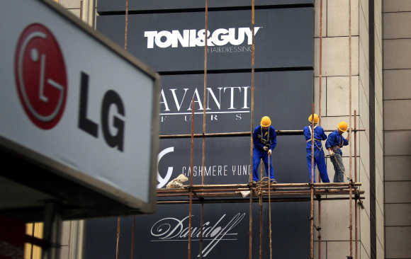 Workers erect scaffolding in front of advertising signs for foreign stores at a shopping mall in central Beijing.