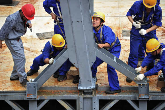 Labourers install a steel pillar at a construction site of the three-storey D3 cafeteria built by the Broad Group in Yueyang, Hunan province.