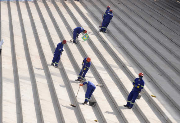 Workers smoothen concrete steps at the construction site of the Corinthians Stadium in the Sao Paulo neighbourhood of Itaquera, Brazil.