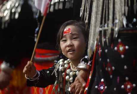 An ethnic Kachin girl waves a National League for Democracy flag