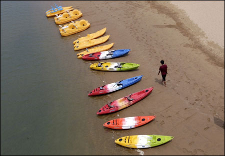 A tourist walks besides kayaks and canoes on Fulong beach in New Taipei city, northeastern Taiwan.
