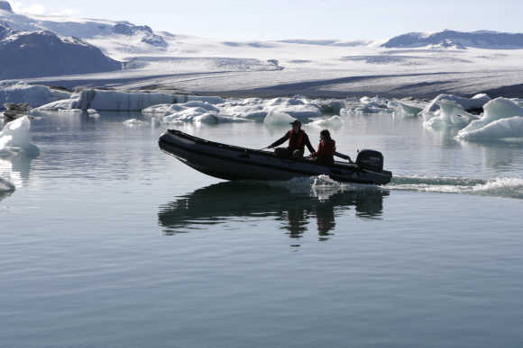 People travel in a boat as they pass blocks of ice from Breidamerkurjokull's Vatnajokull glacier, about 380km from Reykjavik.