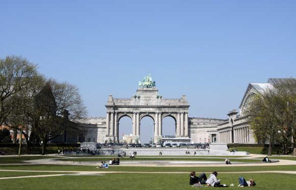 People rest in the Parc du Cinquantenaire of Brussels.