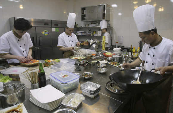 Chefs prepare food inside the kitchen of an A380 theme restaurant in Chongqing municipality, China.