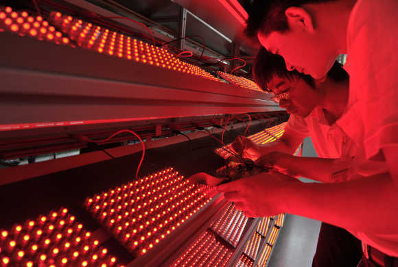 Employees measure the ageing levels of low energy consumption light bulbs at a factory in Nanjing, Jiangsu province, China.