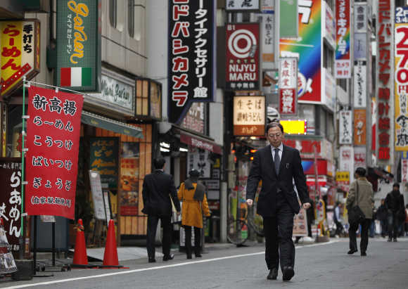 A man walks through a street in Tokyo's Shinjuku district.