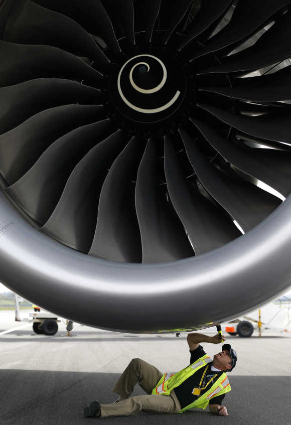 An engineer examines one of the engines of Boeing's new 787 Dreamliner aircraft at Manchester Airport.