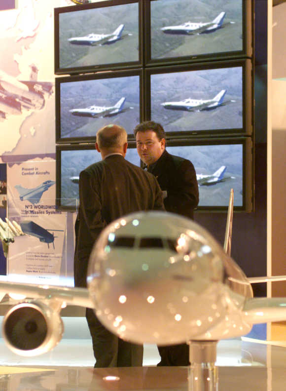 Sales representatives of French aerospace company Aerospatiale Matra chat behind a model of Airbus A340-500 Maken at the Asian Aerospace 2000 held in Singapore.