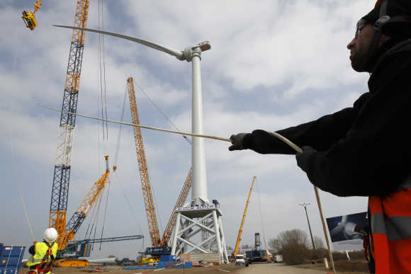 Technicians install a wind turbine blade at Alstom's offshore wind site in Le Carnet, on the Loire Estuary, near Saint Nazaire, France.