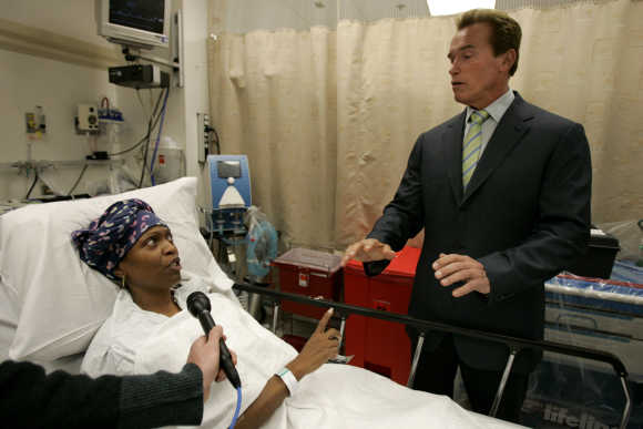 California's then-governor Arnold Schwarzenegger talks to a patient in the hospital.
