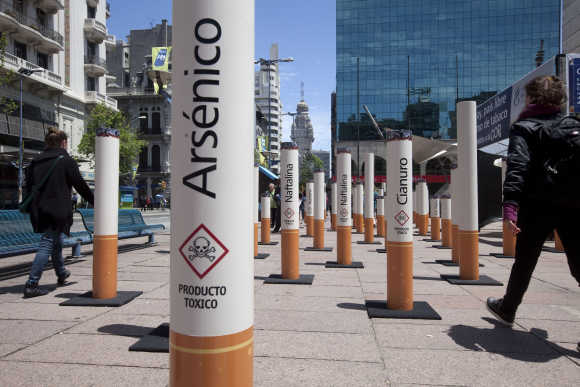 People walk past near an anti-tobacco installation in Montevideo, Uruguay.