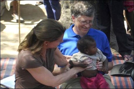 Bill Gates and his wife Melinda hold a child during their visit to a Danapur slum area near Patna on March 23, 2011.
