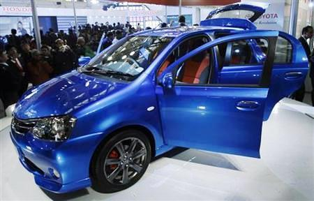 Onlookers stand next to Toyota's compact car 'Etios' at Auto Expo in New Delhi.