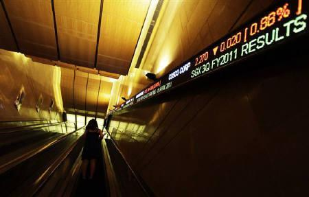 A woman travels up an escalator to attend the Singapore Exchange third quarter results briefing