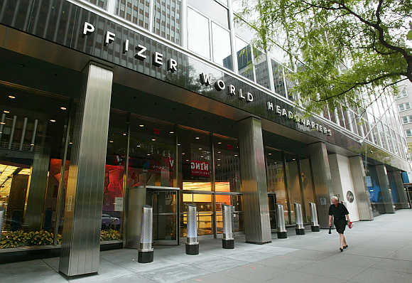 People pass the entrance of Pfizer World headquaters in New York City.