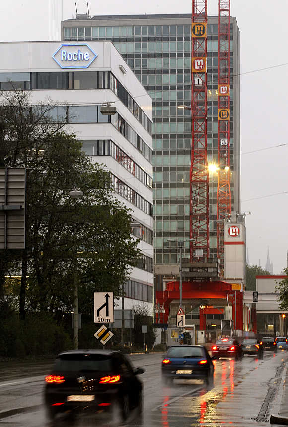 Cars drive past the headquarters of Swiss pharmaceutical company Roche in Basel, Switzerland.