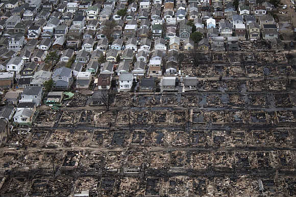 Burnt houses are seen next to those which survived in Breezy Point, a neighbourhood located in the New York City borough of Queens.