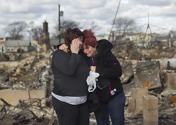 Neighbours Lucille Dwyer, right, and Linda Strong, left, embrace after looking through the wreckage of their homes devastated by fire and the effects of Hurricane Sandy in the Breezy Point section of the Queens borough of New York.