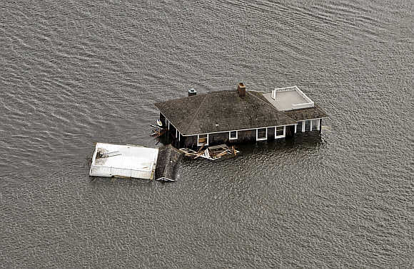 A house floats in the bay after it was washed from its foundation during Hurricane Sandy in Manotoloking, New Jersey.
