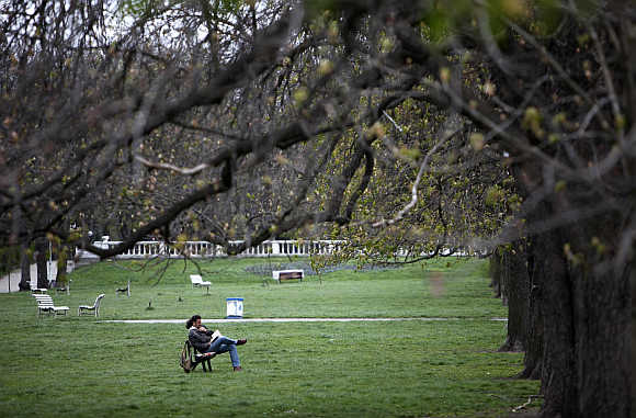 A man reads a book in a park in Sofia.