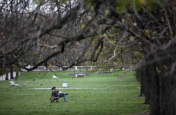 A man reads a book in a park in Sofia.
