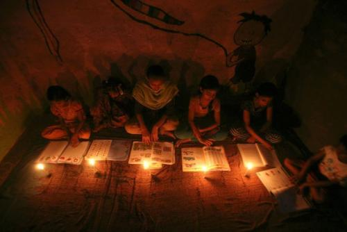 Girls study by candlelight inside a madrasa during a power-cut in Noida on the outskirts of New Delhi
