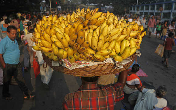 A vendor carries a basket of bananas to sell at a market in Kolkata.