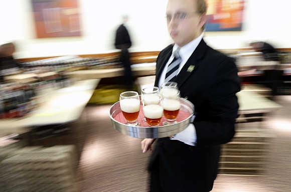 A server walks with a tray of beers during the Brussels Beer Challenge.