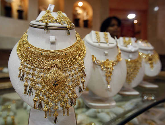 Saleswoman stands behind the showcased gold necklaces at a jewellery showroom in Agartala.