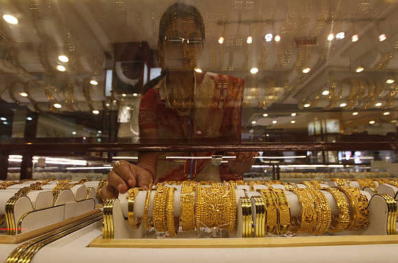 A saleswoman arranges gold jewellery inside a showroom in Kolkata.
