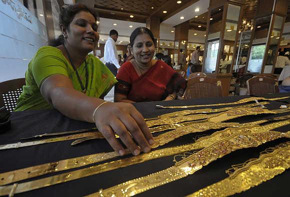 A woman checks a gold waist belt inside a jewellery shop in Hyderabad.