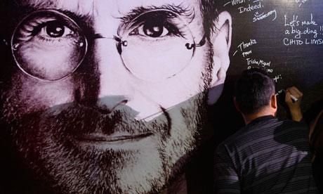 A man signs his name on a sympathy board set up for 'Steve Jobs Day'