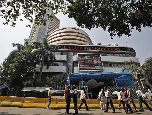 Commuters walk past the BSE building in Mumbai.