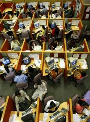 Employees seated in their cubicles at a call centre provide service support to international customers, in Bangalore