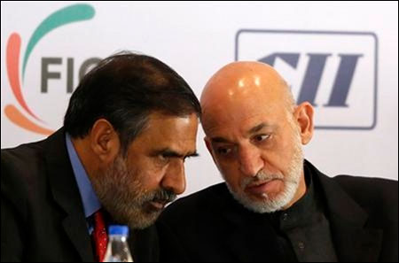 Afghanistan's President Hamid Karzai (R) speaks with Trade Minister Anand Sharma during a business conference in Mumbai November 10, 2012. Karzai is on a five-day state visit to India.
