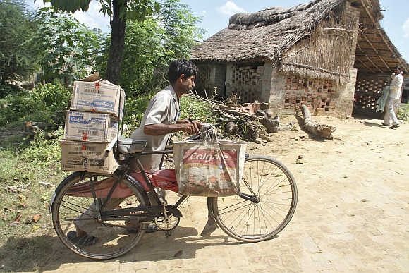 A salesman pushes his bicycle ladened with Colgate products in Hargaon, Uttar Pradesh.