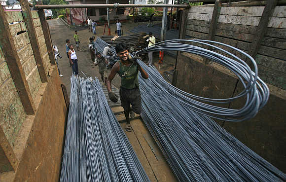 Labourers load iron rods onto a vehicle on the outskirts of Agartala, Tripura.