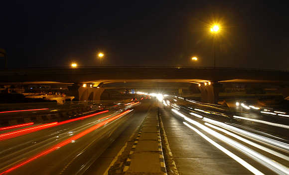 Traffic moves under a flyover along a busy road in New Delhi.