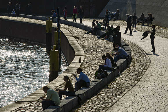 People relax on river Spree embankment on sunny spring day in Berlin.