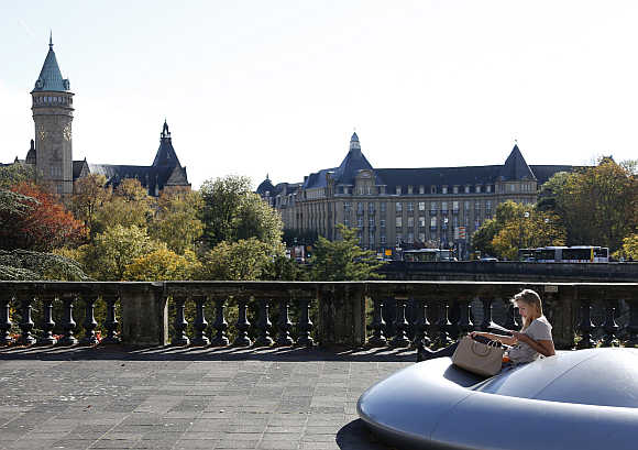 A woman reads during a sunny day in the city of Luxembourg.