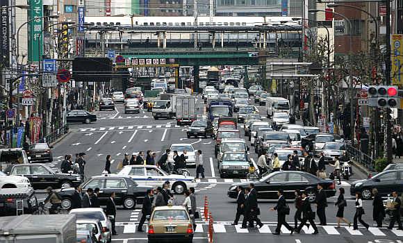 Pedestrians walk across a zebra crossing in Tokyo.