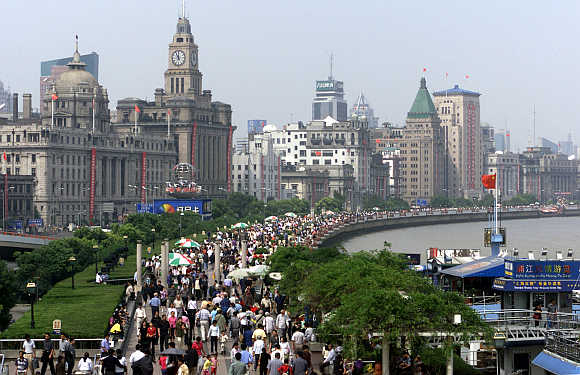 Thousands of tourists crowd along riverside Bund in Shanghai.