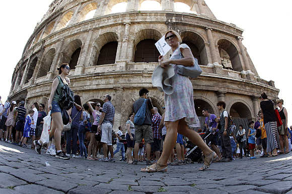 Tourists walk in front of Rome's ancient Colosseum