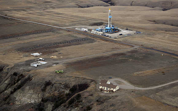 An oil drilling rig operates near homes and farm fields outside Williston, North Dakota.