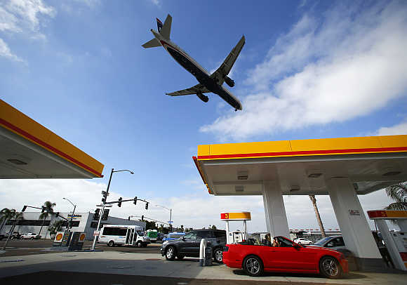 Consumers buy petrol as a plane approaches to land at the airport in San Diego, California.