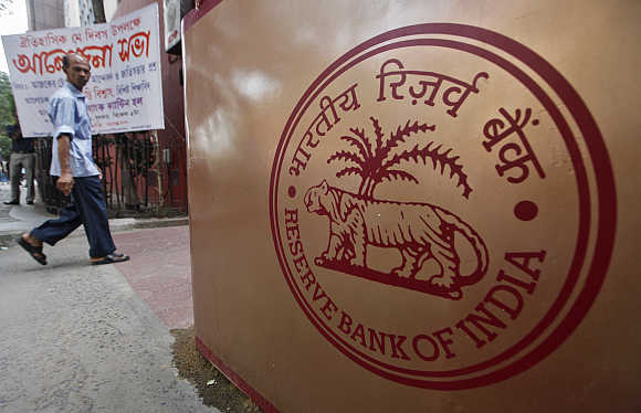 A man walks past an RBI logo in front of its building in Kolkata.